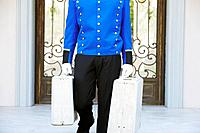 Bellhop carrying suitcases