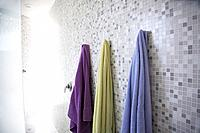 Gray tiled shower stall with bright colored towels