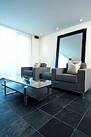 Two gray armchairs in slate tiled living room