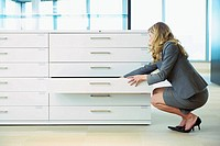 Businesswoman looking through filing cabinet