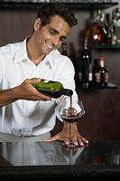 Bartender pouring a glass of red wine
