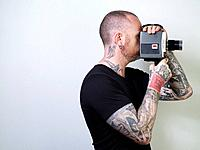 Man wearing tattoos with vintage movie camera, side view, studio shot