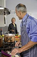 Mature man chopping eggplant, looking at wife, smiling