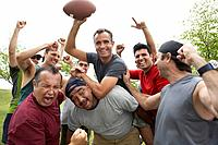 Man raising soccer ball celebrating with friends in park, smiling