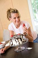 Woman posing with strawberry and cake