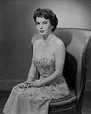 Woman wearing dress sitting on chair, portrait