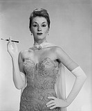 Woman wearing evening dress, holding cigarette, portrait