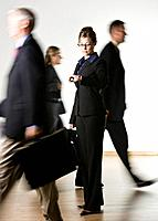 Business woman looking at watch, others passing by blurred motion