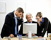 Group of business people looking at computer