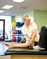 Female physical therapist wrapping athlete´s knee, smiling