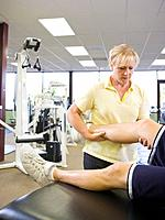 Female physical therapist working with male athlete´s leg in gym