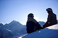 Young man and woman sitting on snow, looking mountain panorama, Kuehtai, Tyrol, Austria