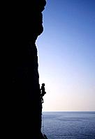 Kalymnos, Greece a woman climbs on a vertical rock pillar above the Aegean Sea, Europe, MR