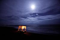 A young woman lying in a four poster bed on the beach in the moonlight, near Uluwatu, Bali, Indonesia