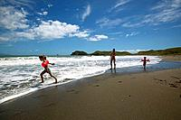 Children playing with their mother on the beach, Port Jackson on the northern tip of Coromandel Peninsula, North Island, New Zealand