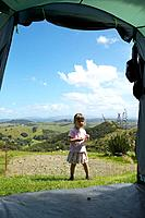 Girl in front of family tent, camping at Okopako Lodge, near Opononi, at Hokianga Harbour, Northland, North Island, New Zealand