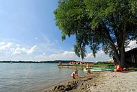 Sandy beach at lake Simssee with family with three children and kayak, Chiemgau, Upper Bavaria, Bavaria, Germany