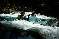Man, guide, paddling through whitewater, kayak weekend for beginners on the Mangfall river, Upper Bavaria, Germany