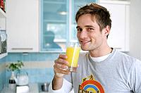 Young man drinking a glass of orange juice, Munich, Germany