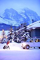 Skiers and van in front of Lake Louise Inn, Lake Louise, Alberta, Canada