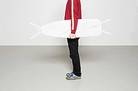Man holding ironing board like surfboard