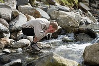 A man washing his face in the stream