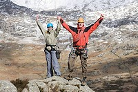 A couple with raised arms on rocks