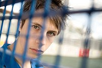 Teenage boy behind fence