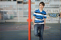 Teenage boy leaning on fence