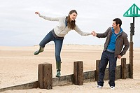 Couple playing on wooden fence at beach