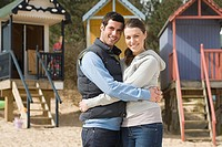 Couple hugging near beach huts