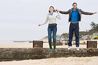 Couple jumping off fence at beach