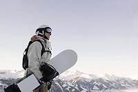 A woman holding a snowboard
