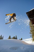 A snowboarder jumping off a cabin roof