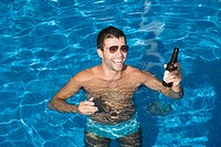 Man drinking beer in swimming pool