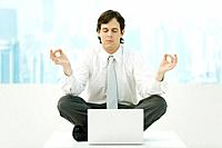 Businessman meditating in office, eyes closed