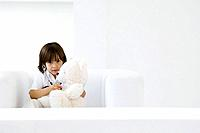 Little boy playing doctor with teddy bear, using stethoscope (thumbnail)