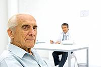 Doctor working at desk, focus on senior patient in foreground