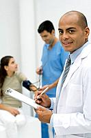 Doctor writing on clipboard, smiling at camera, nurse measuring patient's blood pressure in background