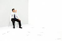 Young professional man sitting in corner, throwing paper airplanes