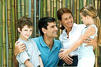 Family smiling at each other in front of bamboo, group portrait, boy looking at camera (thumbnail)