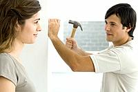 Couple smiling at each other, man hammering nail into wall (thumbnail)