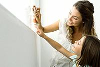 Mother cleaning window, daughter pointing out another spot, both smiling