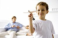 Boy playing with toy airplane, parents sitting on couch in background