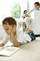 Little boy lying on floor and reading book, parents reading on sofa in background