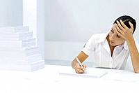 Woman holding her forehead, writing on blank sheet of paper, looking at staggered pile of paper