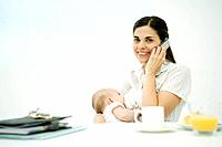 Woman sitting at breakfast table, breast feeding baby, using cell phone, smiling at camera