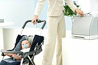 Professional woman in office with baby in stroller, using printer, cropped view