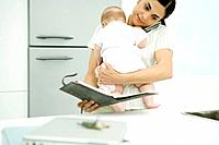 Woman holding baby, using cell phone and looking at agenda