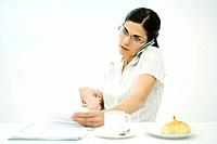Professional woman sitting at breakfast table, holding baby, using cell phone and studying document